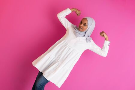 young afro beauty wearing traditional islamic clothes on plastic pink background  gender strenght Stock Photo