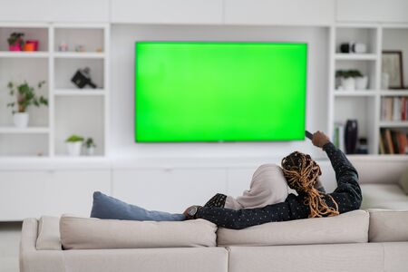 African Couple Sitting On Sofa Watching TV Together Chroma Green Screen Woman Wearing Islamic Hijab Clothes Stock Photo