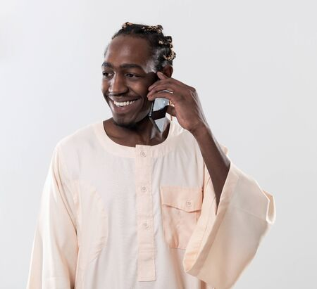african man using smartphone and wearing traditioinal sudan clothes