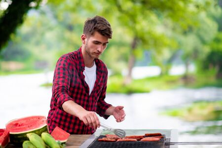 Man cooking tasty food on barbecue grill for outdoor french dinner party near the river on beautiful summer evening in nature