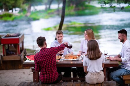 group of happy friends having picnic french dinner party outdoor during summer holiday vacation  near the river at beautiful nature