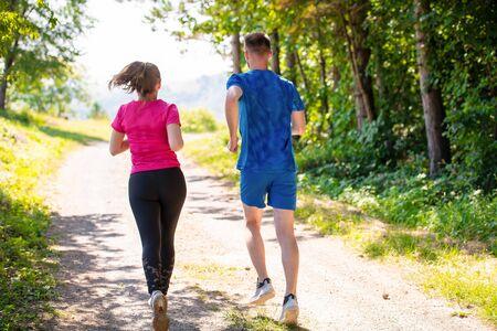 junges glückliches Paar, das einen gesunden Lebensstil genießt, während es auf einer Landstraße durch den schönen sonnigen Wald joggt, Bewegungs- und Fitnesskonzept