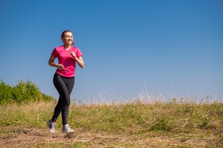 young happy woman enjoying in a healthy lifestyle while jogging on a meadow at beautiful sunny summer mountain, exercise and fitness concept