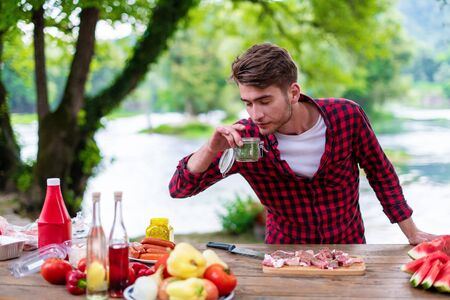 young man putting spices on raw meat for barbecue grill during outdoor french dinner party near the river on beautiful summer evening in nature