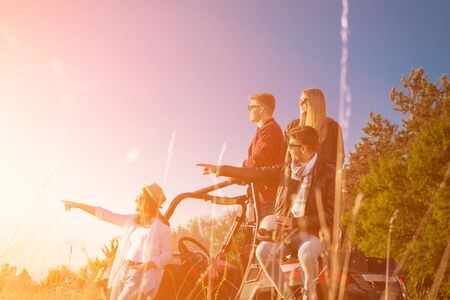 portrait of group young happy people enjoying beautiful sunny day while driving a off road buggy car on mountain nature Imagens