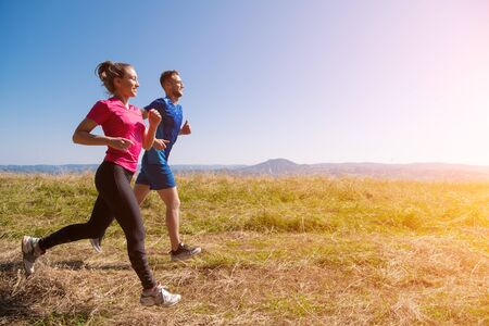 young happy couple enjoying in a healthy lifestyle while jogging on a meadow at beautiful sunny summer mountain, exercise and fitness concept
