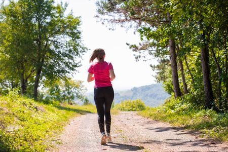 young happy woman enjoying in a healthy lifestyle while jogging on a country road through the beautiful sunny forest, exercise and fitness concept Imagens