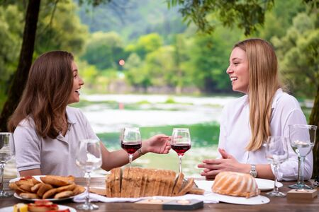 two young happy girlfriends having picnic french dinner party outdoor during summer holiday vacation  near the river at beautiful nature Imagens