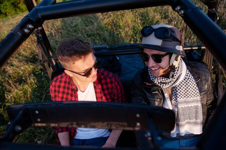 two young happy excited men enjoying beautiful sunny day while driving a off road buggy car on mountain nature