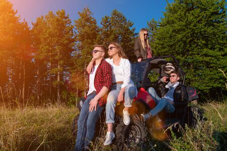 portrait of group young happy people enjoying beautiful sunny day while driving a off road buggy car on mountain nature Reklamní fotografie