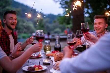 group of happy friends celebrating holiday vacation using sprinklers and drinking red wine while having picnic french dinner party outdoor near the river on beautiful summer evening in nature Banque d'images