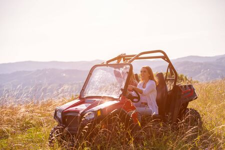 two young happy excited women enjoying beautiful sunny day while driving a off road buggy car on mountain nature Reklamní fotografie