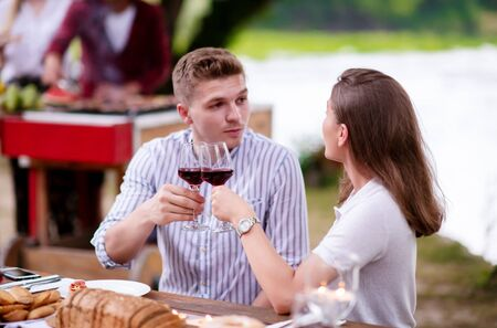 young happy couple toasting red wine glass while having picnic french dinner party outdoor during summer holiday vacation  near the river at beautiful nature Imagens