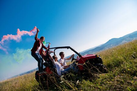 group of young happy excited people having fun enjoying beautiful sunny day holding colorful torches while driving a off road buggy car on mountain nature