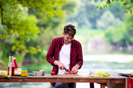 young man cutting vegetables for salad or barbecue grill during outdoor french dinner party near the river on beautiful summer evening in nature Banco de Imagens - 132047799