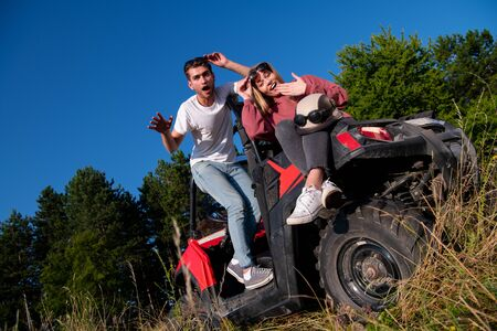 portrait of young happy excited couple enjoying beautiful sunny day while driving a off road buggy car on mountain nature Reklamní fotografie