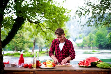 young man cutting raw meat for barbecue grill during outdoor french dinner party near the river on beautiful summer evening in nature