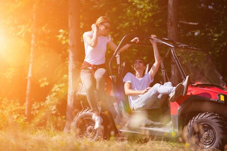 portrait of young happy excited couple enjoying beautiful sunny day while driving a off road buggy car on mountain nature Imagens