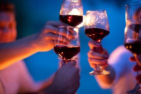 groupe d'amis heureux grillant un verre de vin rouge tout en pique-niquant un dîner français en plein air pendant les vacances d'été près de la rivière par une belle soirée dans la nature