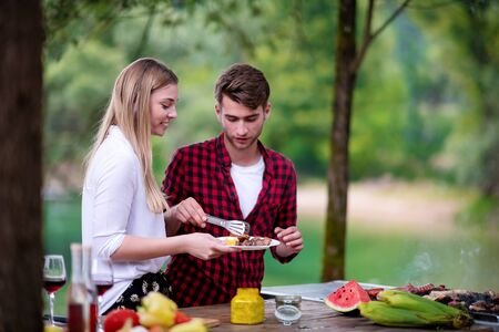 happy couple having picnic french dinner party outdoor during summer holiday vacation  near the river at beautiful nature Imagens