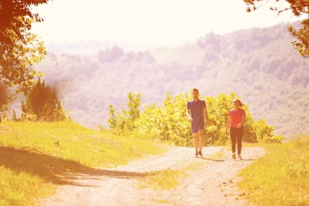 young happy couple enjoying in a healthy lifestyle while jogging on a country road through the beautiful sunny forest, exercise and fitness concept