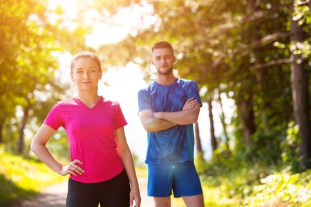 portrait of young happy couple enjoying in a healthy lifestyle while jogging on a country road through the beautiful sunny forest, exercise and fitness concept