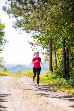 young happy woman enjoying in a healthy lifestyle while jogging on a country road through the beautiful sunny forest, exercise and fitness concept Фото со стока