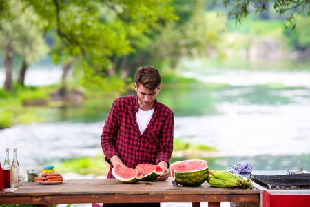 young man cutting juicy watermelon during outdoor french dinner party near the river on beautiful summer evening in the nature