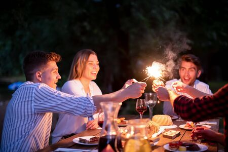 group of happy friends celebrating holiday vacation using sprinklers and drinking red wine while having picnic french dinner party outdoor near the river on beautiful summer evening in nature