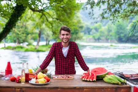 young man putting spices on raw meat for barbecue grill during outdoor french dinner party near the river on beautiful summer evening in nature Banco de Imagens - 132047761