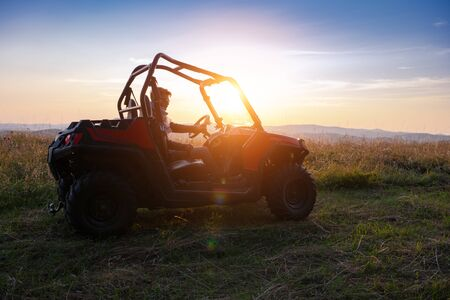 portrait of young happy excited man enjoying beautiful sunny day while driving a off road buggy car on mountain nature