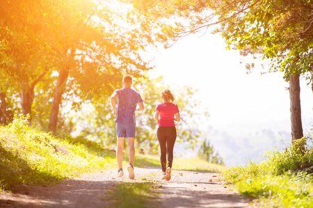 jeune couple heureux profitant d'un mode de vie sain tout en faisant du jogging sur une route de campagne à travers la belle forêt ensoleillée, concept d'exercice et de remise en forme