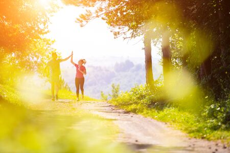 young happy couple enjoying in a healthy lifestyle giving high five to each other after jogging on a country road through the beautiful sunny forest, exercise and fitness concept Imagens