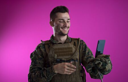army soldier using smartphone to contact family or girlfriend communication and nostalgia concept pink background Stock Photo