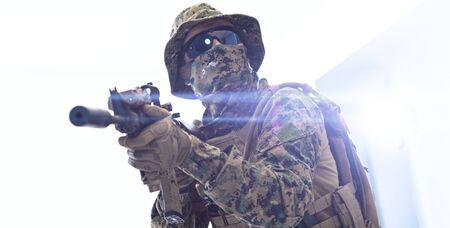 modern warfare american marines soldier aiming  in combat position and searching for target isolated on white background