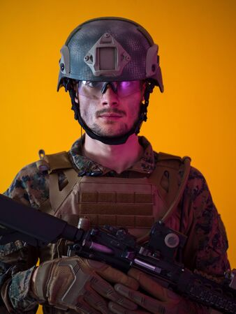 modern warfare marine soldier with fire arm weapon and protective army tactical gear clothes Studio shot on  isolated yellow background