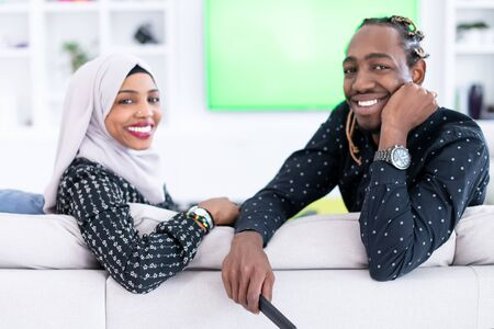 African Couple Sitting On Sofa Watching TV Together Chroma Green Screen Woman Wearing Islamic Hijab Clothes
