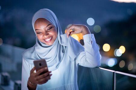 Jeune femme musulmane moderne portant un foulard dans la rue de la ville urbaine la nuit envoyant des SMS sur un smartphone avec la lumière de la ville bokeh en arrière-plan Banque d'images