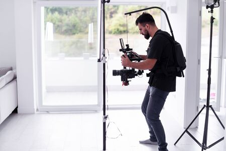 Professional videographer with gimball video slr recording video on professional camera at home