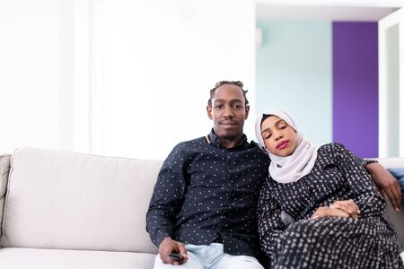 African Couple Sitting On Sofa Watching TV Together Chroma Green Screen Woman Wearing Islamic Hijab Clothes Stockfoto