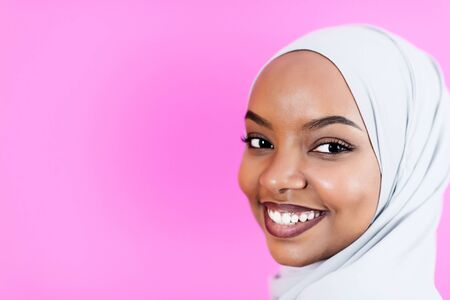 portrait of young modern muslim afro beauty wearing traditional islamic clothes on plastic pink background