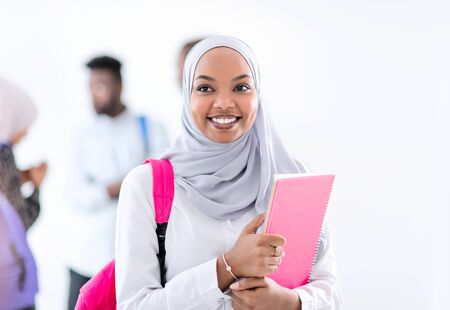 portrait of young african modern muslim female student with group of friends in background  wearing traditional Islamic hijab clothes