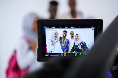 male videographer in white digital studio recording video on professional camera by shooting happy african students standing together against white background girls wearing traidiional sudan muslim hijab fashion