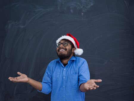 Indian man wearing traditional Santa Claus hat on chalkboard  background studio dark-skinned Christmas santa new year party