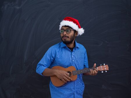 Indian man wearing Santa Claus Christmas red hat and playing Latin America traditional small guitar Banco de Imagens