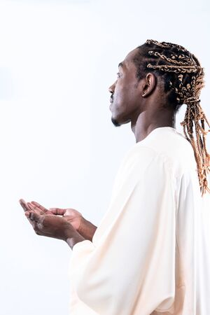 Handsome Young  African Muslim Man Making Traditional Fatiha Prayer To Allah God While Wearing A Traditional Sudan fashion clothes in studio
