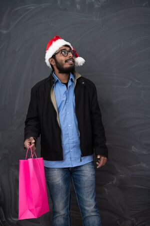 Indian  man wearing party clothes in Santa hat with shopping bag on dark  background studio dark skinned middle eastern Santa Claus merry Christmas Banco de Imagens