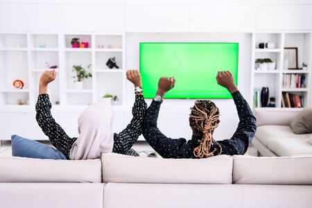 African Couple Sitting On Sofa Watching TV Together Chroma Green Screen Woman Wearing Islamic Hijab Clothes Banco de Imagens