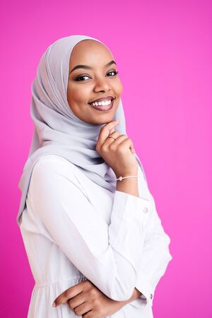 portrait of young modern muslim afro beauty wearing traditional islamic clothes on plastic pink background Banco de Imagens