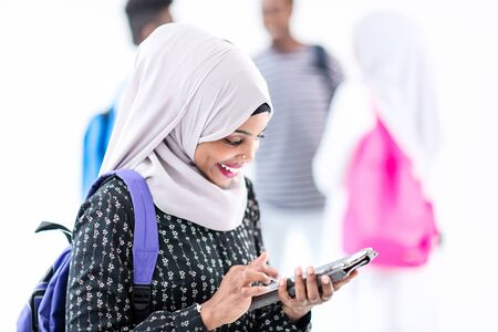 young modern muslim african female student using tablet computer with group of friends in background  wearing traditional Islamic hijab clothes Banco de Imagens